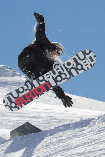 Snowboarder jumping, shot against the light